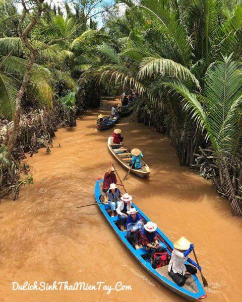 Du khách ngồi trên đò chèo qua các rạch dừa nước xanh mát